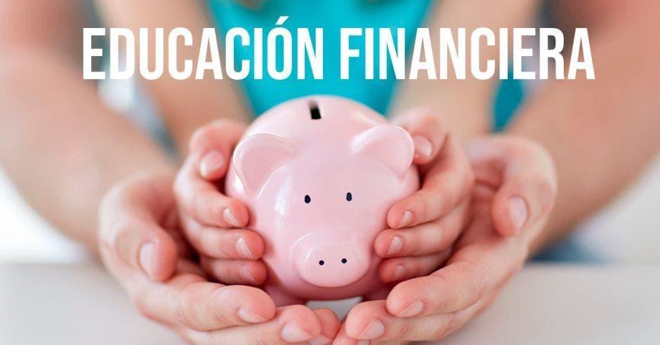 Manos, alcancía, educación financiera
