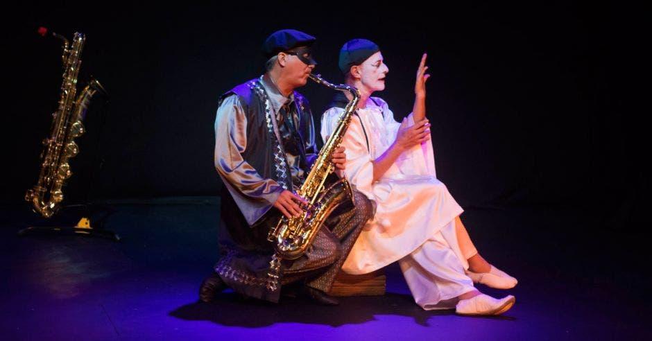Dos de los artistas que participan en la función, uno con saxofón y el otro con la cara pintada de mimo