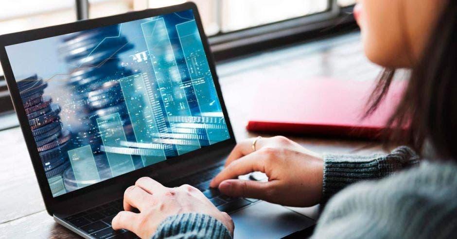 Una mujer en frente de la computadora, revisando sus finanzas