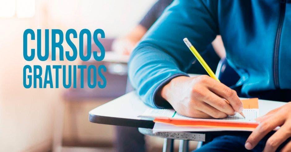 Una persona en un pupitre con un lápiz y un cuaderno a la par dice Cursos Gratuitos