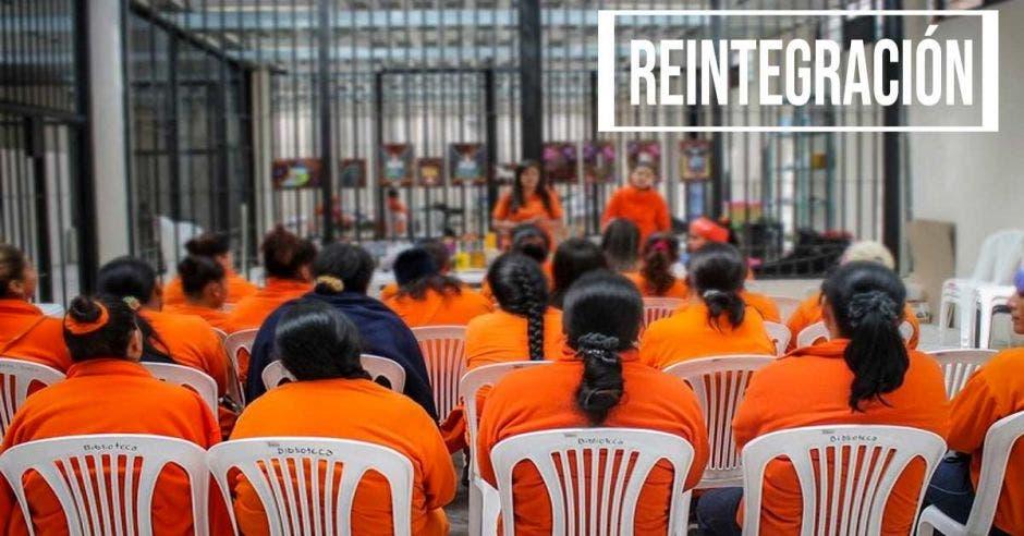 Un grupo de mujeres privadas de libertad, recibiendo una charla afuera de sus celdas