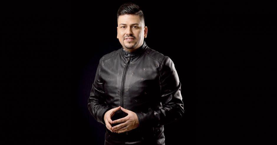 El maquillista Jonathan Núñez con una sueter negra en un fondo negro