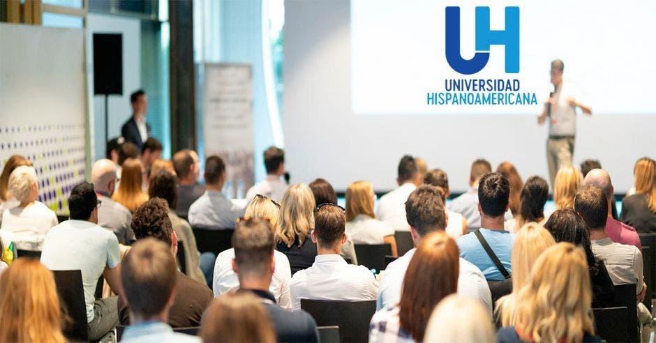 Una sala de conferencias con un logo de la Universidad Hispanoamericana