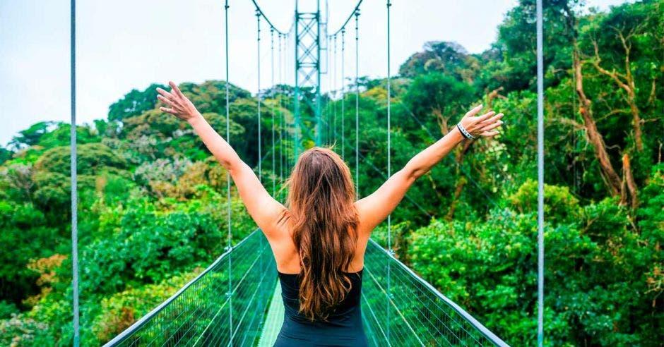 mujer en puente colgante en medio del bosque