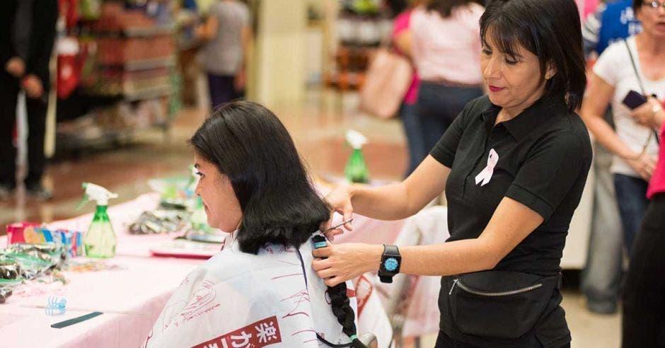 mujer cortándole el cabello a otra