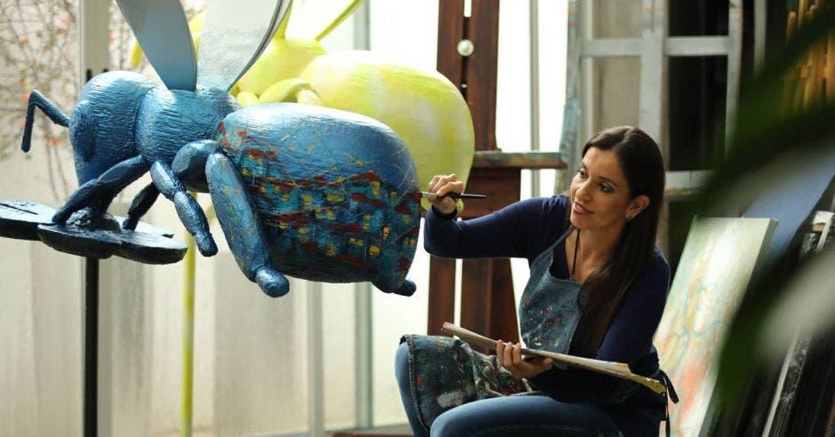 Una mujer pinta una escultura de una abeja