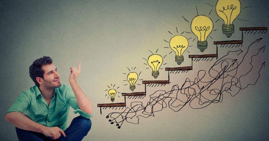 Un joven viendo una escalera llena de luces que simulan ideas