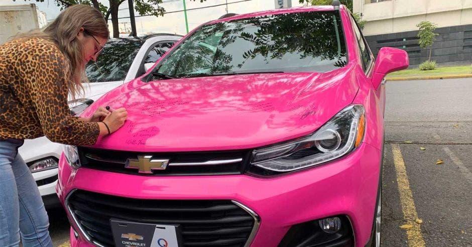 mujer firmando en carro rosado
