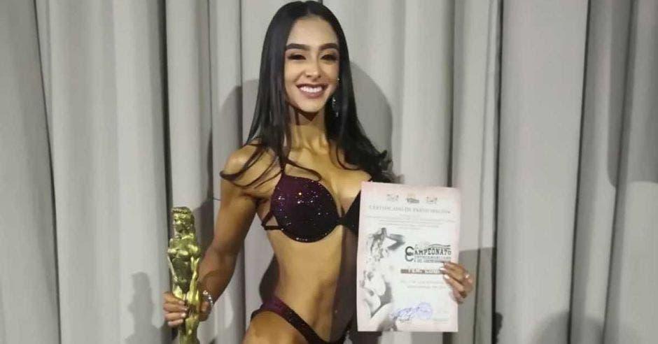 Mujer en vestido e baño y trofeo en mano