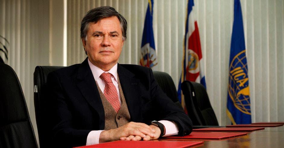 Manuel Otero en un escritorio con varias banderas