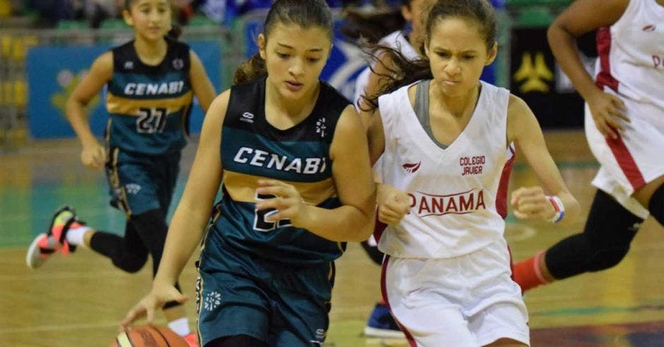 mujeres luchando un balón en basket