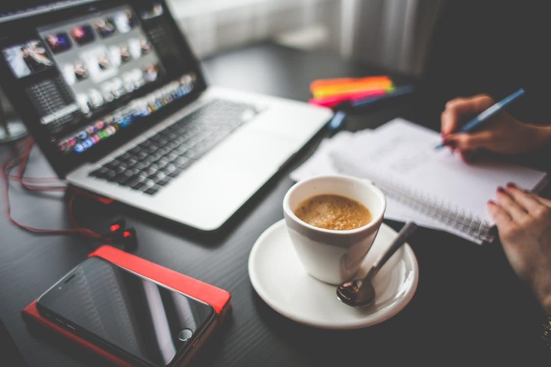 Una laptop, una taza de café y una persona escribiendo