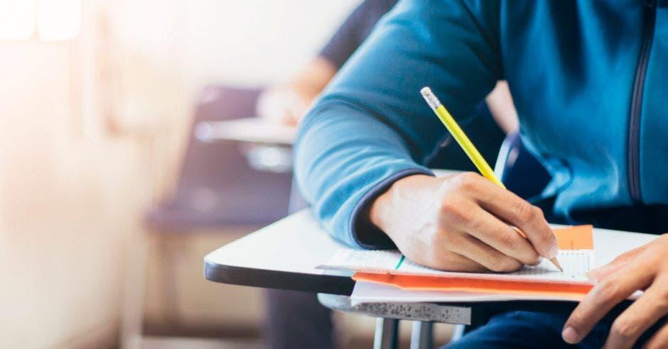 Una persona en un pupitre haciendo un examen