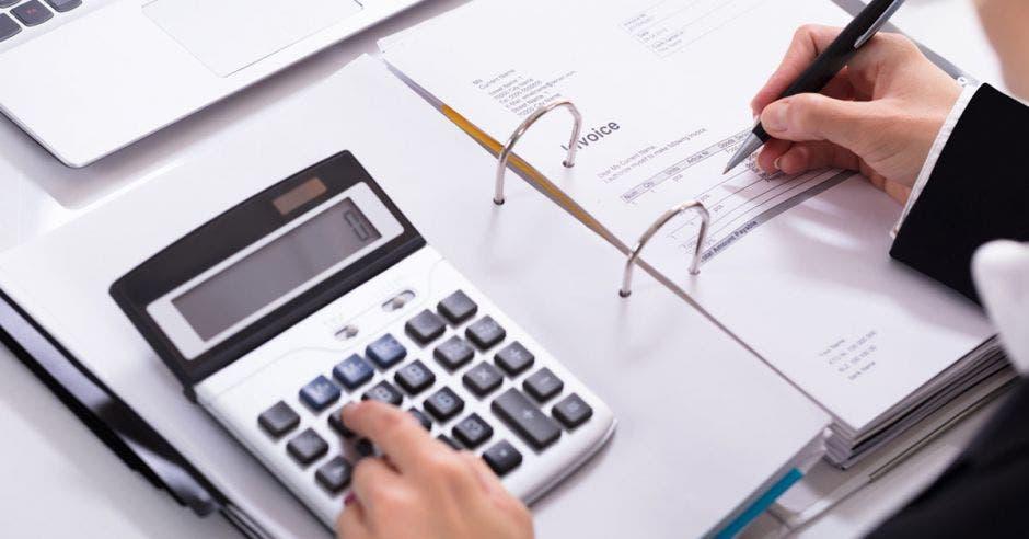 Una persona sumando en una calculadora