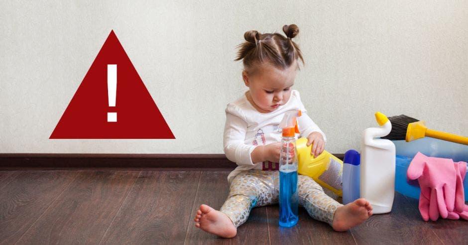 Una niña jugando con productos de limpieza y un símbolo de alerta
