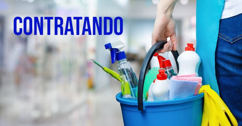 Una mano sosteniendo un balde cargado de productos de limpieza y la palabra contratando