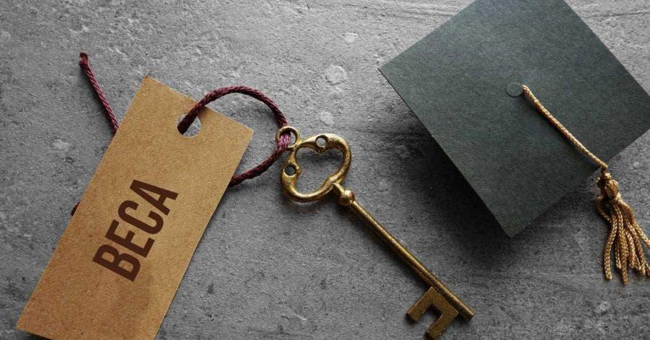 Una llave con un papel que dice beca y un birrete al lado