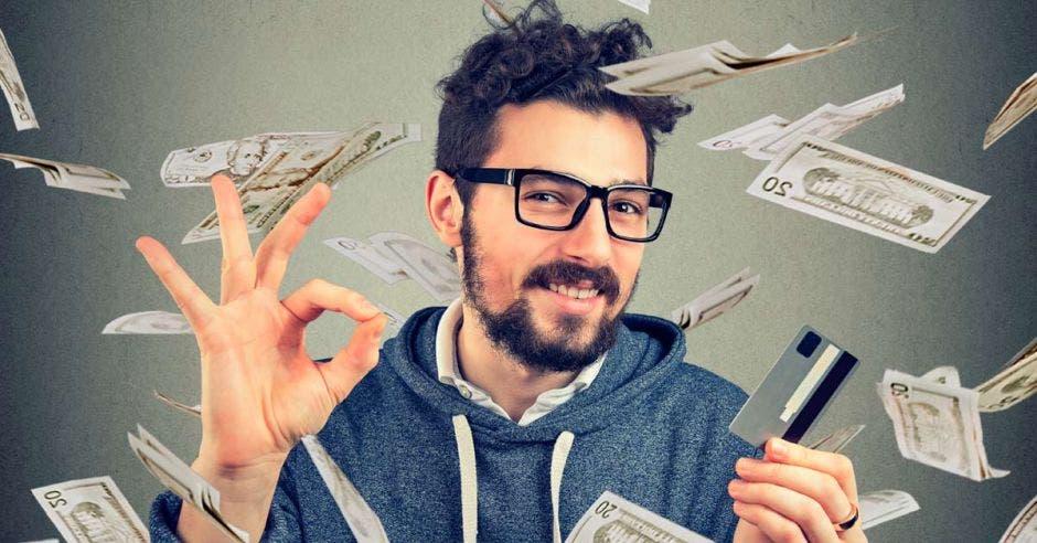 Persona con tarjeta de crédito en la mano y billetes volando