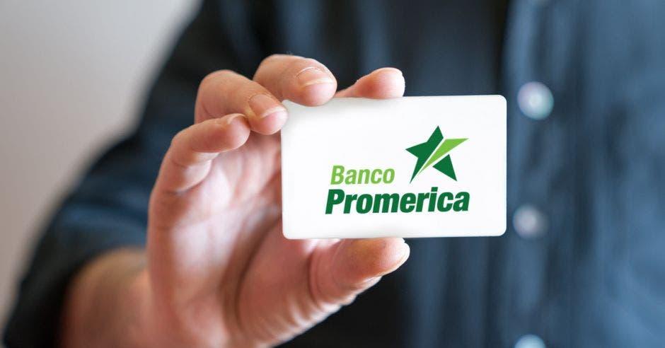 Mano sosteniendo tarjeta con logo de Banco Promerica