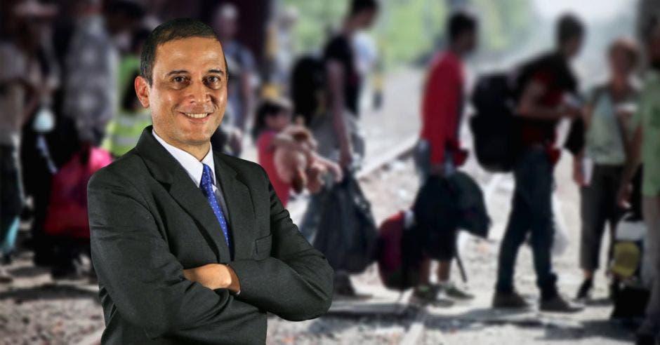 Luis Diego Calderón, gerente financiero de la Caja y al fondo una fila de refugiados