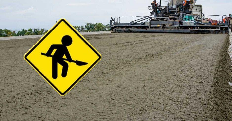 Cemento sobre calle y señal de tránsito de trabajos en la vía