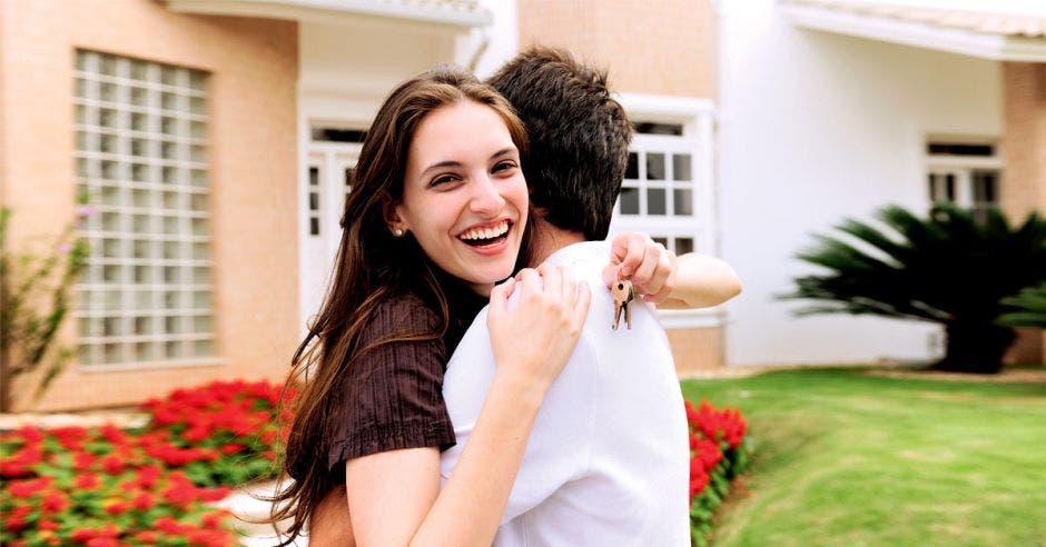 Dos jóvenes abrazados frente a una casa