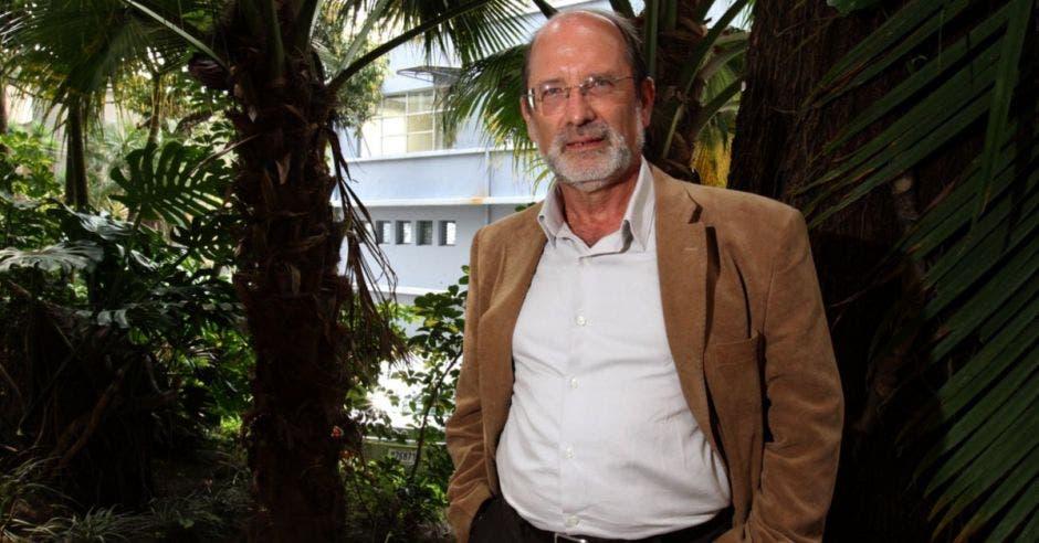 Henning Jensen, rector de la Universidad de Costa Rica entre unos árboles