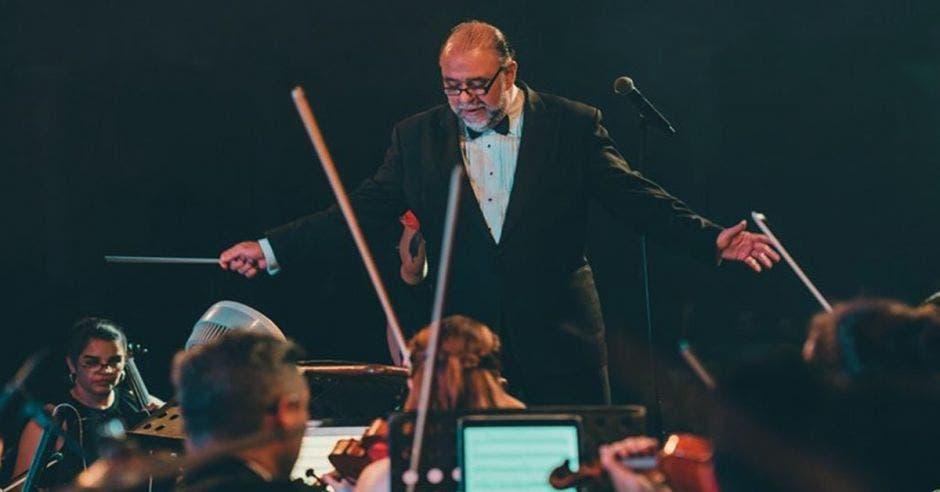 El director de la Filarmónica en medio del escenario dando instrucciones a la orquesta