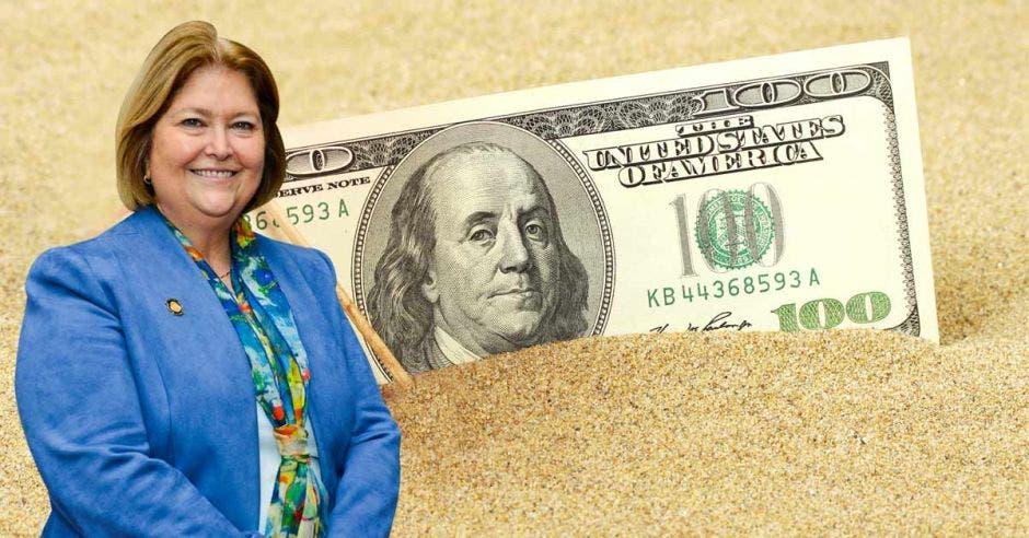 María Amalia Revelo, ministra de Turismo, posa junto a un billete de un dólar en la playa