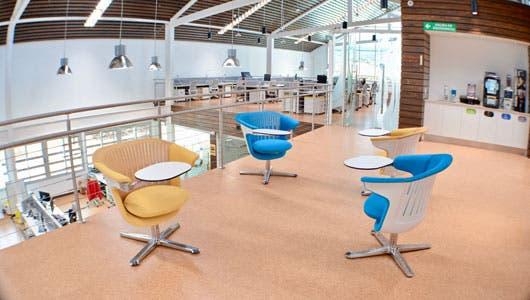 Un grupo de sillas de varios colores en una segunda planta de un edificio