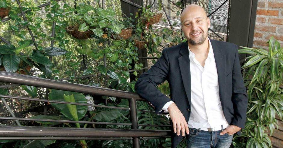 Federico Cartín arrecostado a una varanda mira la cámara