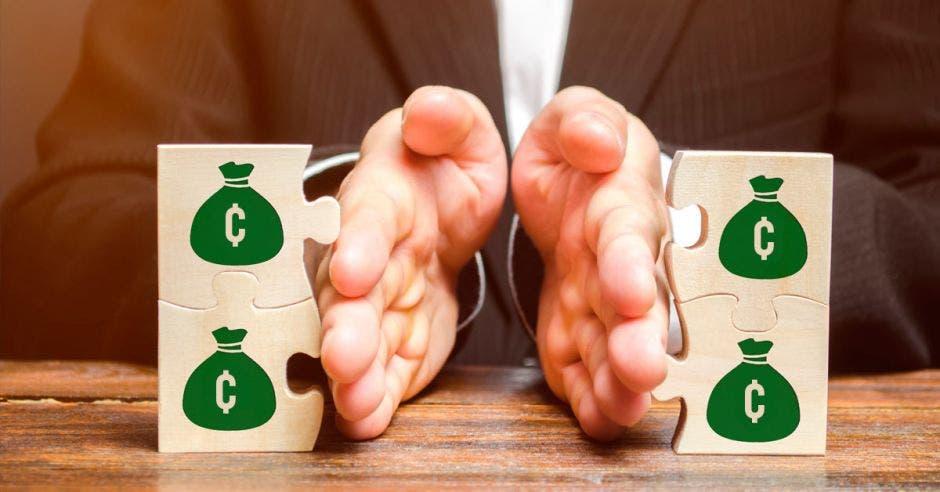 Manos separando piezas de rompecabezas con signos de bolsas de dinero