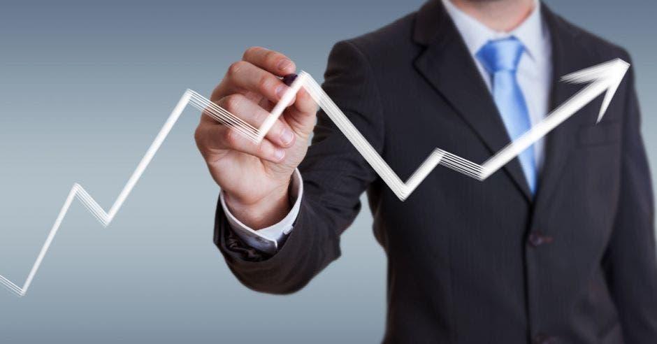 Persona con traje entero negro dibujando un gráfico lineal blanco con su mano.