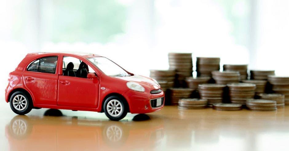 un carro color rojo en miniatura y en el fondo unas monedas