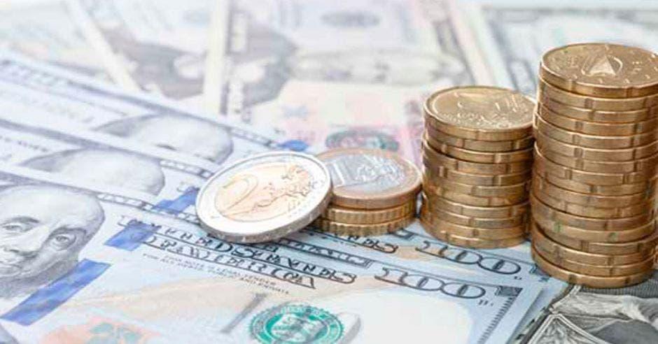 billetes de dólares con monedas encima agrupadas para arriba
