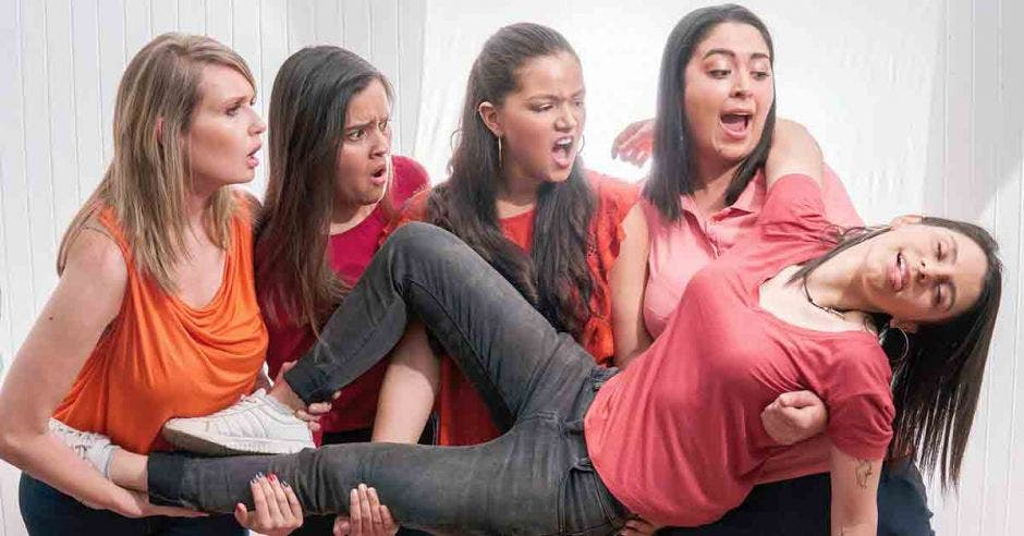 Cuatro mujeres sostienen a otra que está actuando como desmayada