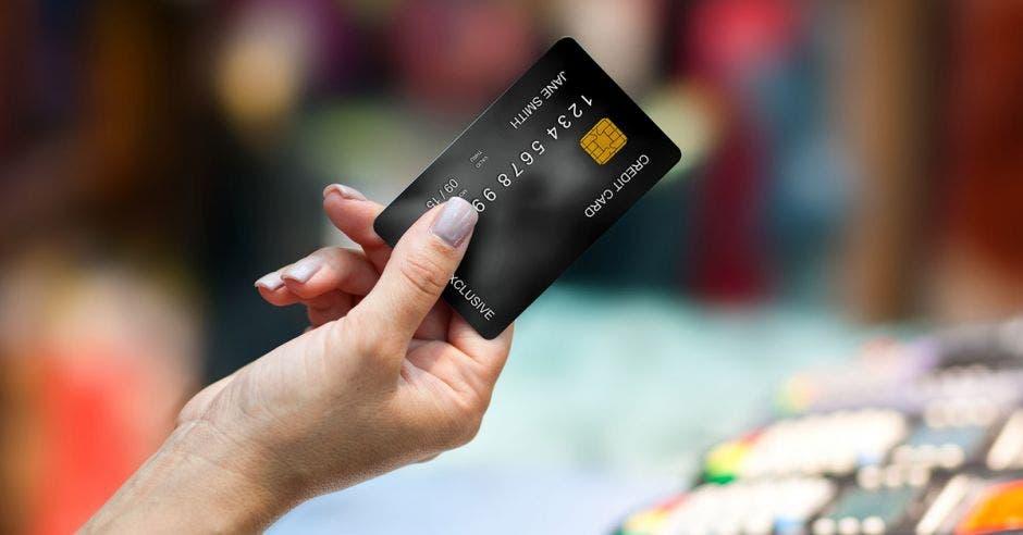 Una mano de mujer presentando una tarjeta de crédito de color negro.