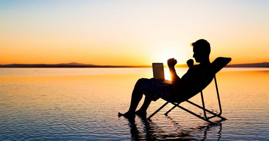 Persona en silla de playa, sentada frente al mar, en un atardecer, con computadora en sus piernas y brazos asemejando celebración