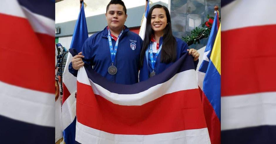 hombre y mujer posan con bandera de costa rica