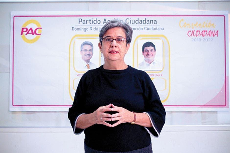 Margarita bolaños con una blusa negra posa frente a un fondo que simula una papeleta de votacion, en donde se ve una imagen del logotipo del PAC