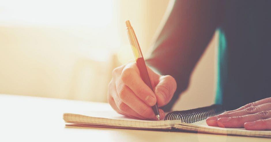 Una persona con un cuaderno y un lapicero