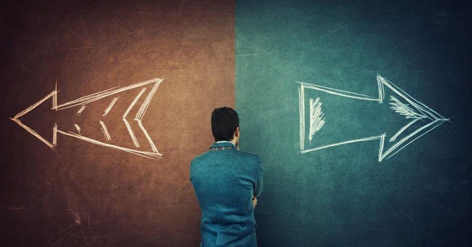 Un hombre de espalda mira una pared, la cual, está dividida por una raya vertical, cada uno de los lados tiene un color diferente, café y verde y sobre el muro, se ven dos señales de dirección con caminos opuestos