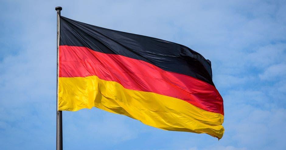 Una bandera de Alemania ondea en el cielo color claro