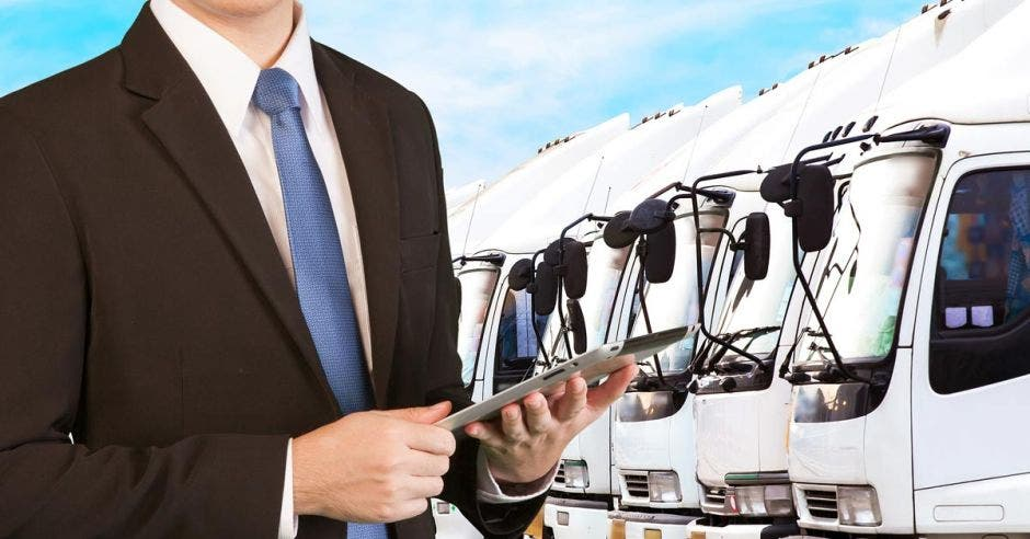 Un hombre con traje y una tableta posa frente a una flotilla de vehículos