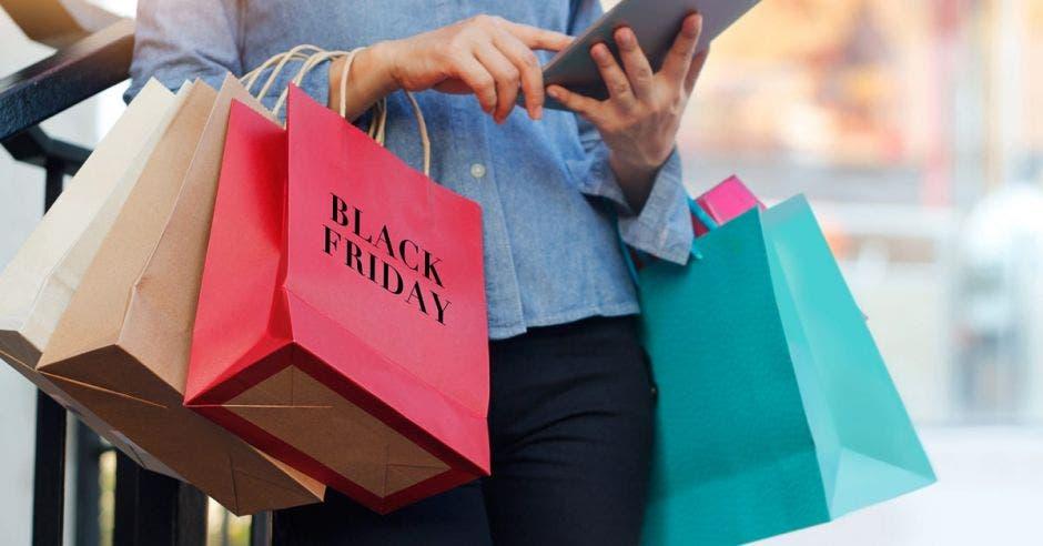 mujer cargando bolsas de compras de color café, verde y rosada que dice black friday.