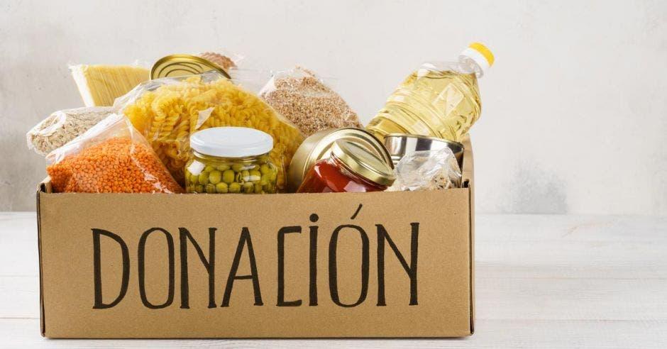 caja de cartón con la palabra donación llena de alimentos variados