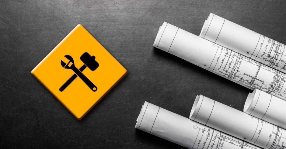 fondo negro con planos al lado derecho, al lado izquierdo, signo de contrucción amarillo de martillo y llave francesa