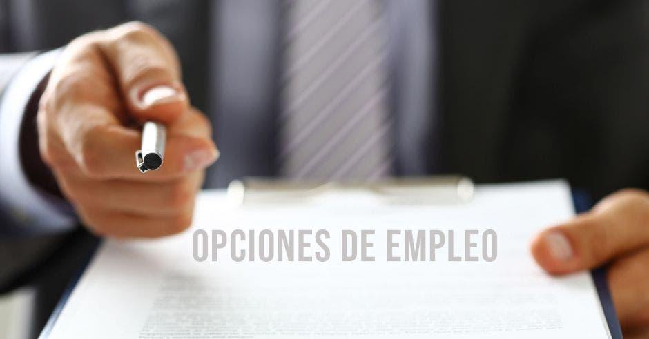 Persona con un bolígrafo señala el contrato para que la otra persona firme y sea contratada