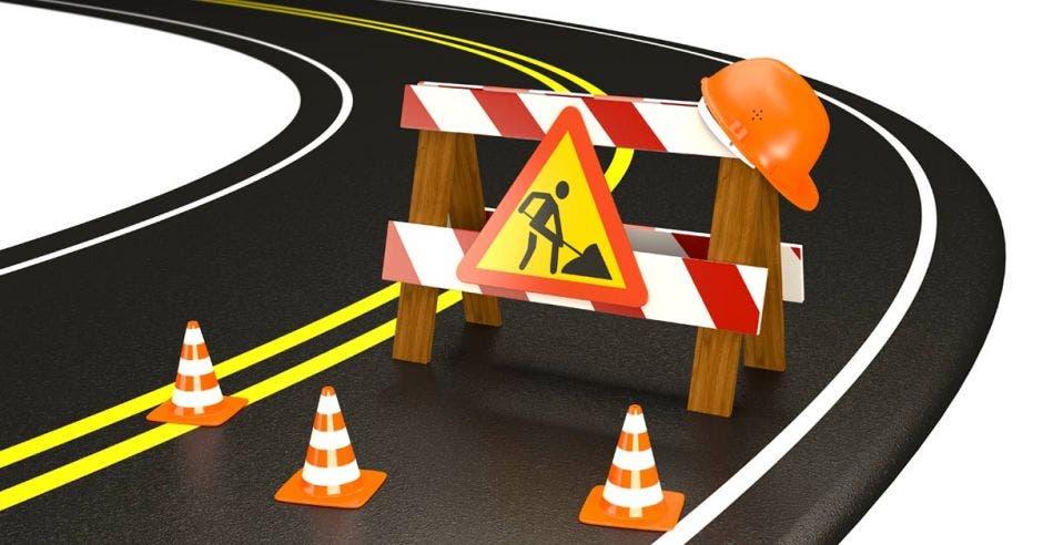 Una imagen de un letrero con el señal de hombres trabajando rodeada de conos en medio de una carretera
