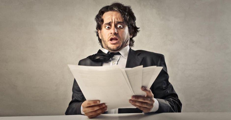 un hombre se asusta al ver facturas.